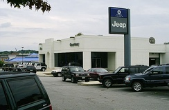 Typical car dealership (in this case a Jeep dealer) selling used cars outside, new cars in the showroom, as well as a vehicle entrance to the parts and service area in the back of the building