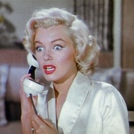 Monroe in Gentlemen Prefer Blondes. She is wearing a white dressing gown and is holding a phone. She looks shocked, with wide eyes and an open mouth.