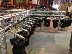 Moving lights hanging on a truss, ready for rigging and chain motors.