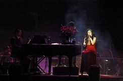 A woman in a red dress sings into a hand-held microphone while sitting on a chair beside a piano during a concert