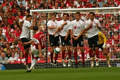 Robin van Persie takes a free kick as Fulham players form a defensive wall.