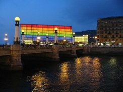Night view of Kursaal Palace lit up with Rainbow flag colors.