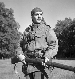 Sergeant H.A. Marshall of The Calgary Highlanders. Canadian snipers in the Second World War were trained scouts. Specialized equipment includes Lee–Enfield No. 4 Mk I(T) rifle and scope combination and a camouflaged Denison smock. PAC Photo, by Ken Bell (September 1944).