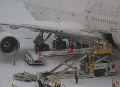 Loading luggage onto a Boeing 747 at Boston Logan Airport, during snow