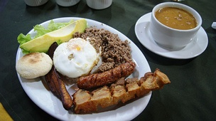 A traditional Bandeja paisa meal. A staple dish assembled with several foods making necessary to use a platter. It is made of beans, rice, fried eggs, chorizo, pork rind and other ingredients depending on the location.