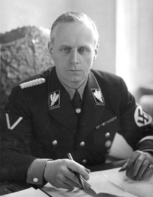 Portrait of a middle-aged man with short grey hair and a stern expression. He wears a dark military uniform, with a swastika on one arm. He is seated with his hands on a table with several papers on it, holding a pen.