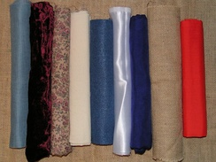 A variety of contemporary fabrics. From the left: evenweave cotton, velvet, printed cotton, calico, felt, satin, silk, hessian, polycotton