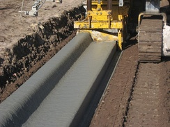 This machine slip casts a concrete curb with integral gutter