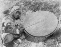 Nunivak Cup'ig man playing a very large drum (cauyaq) in 1927 photograph by Edward S Curtis
