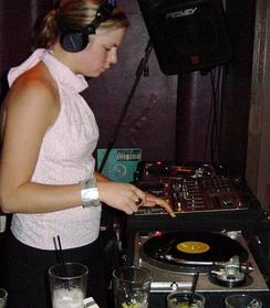 A female DJ mixing two record players at a live event.