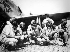 "Pilots of the 332d Fighter Group, ""Tuskegee Airmen,"" the elite, all-African American 332d Fighter Group at Ramitelli Airfield, Italy. From left to right, Lt. Dempsey W. Morgran, Lt. Carroll S. Woods, Lt. Robert H. Nelron, Jr., Capt. Andrew D. Turner, and Lt. Clarence P. Lester."