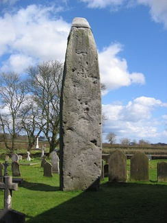 The Rudston Monolith, almost 26ft high, close to Rudston Parish Church of all Saints