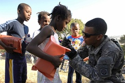 Soldiers distribute aid in Haiti: Member of 82nd Airborne Division's 1st Squadron, 73rd Cavalry Regiment  marks the fingernail of a small girl to indicate she has gone through the distribution line in Port-au-Prince, Jan. 18, 2010.