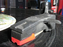 A dusty/scratched vinyl record being played. The dust settles into the grooves.