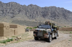 Two Bushmasters passing through a settlement in Afghanistan during April 2010