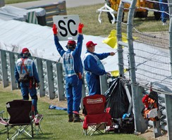 A yellow flag with SC (safety car) sign is shown during the 2006 United States Grand Prix.