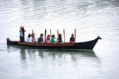 A canoe awaiting traditional invitation to make landfall by the local S'Klallam people at a beach in Port Angeles, Washington, in 2010. Canoes from several Coast Salish groups arrived for a ceremony commemorating the official naming of the Salish Sea.