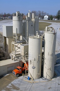 Concrete plant showing a concrete mixer being filled from ingredient silos