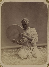 A traditional Central Asian musician from the 1860s or 1870s, holding up his dayereh.