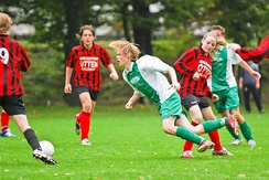 A player (red/black) commits a foul by tripping her opponent (green/white)