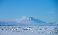 Distant view over an ice-covered sea of a conical mountain