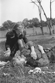 A girl cries over the body of her 14-year-old sister who was strafed by the Luftwaffe