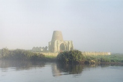 Gatehouse of St Benet's Abbey in the early morning mist, October 2004. The conical structure is the remains of the later windmill built inside it