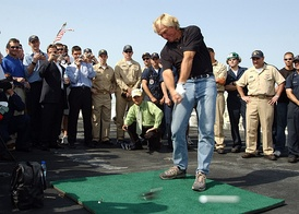 Professional golfer Greg Norman drives a golf ball off the flight deck of USS John F. Kennedy (CV67)