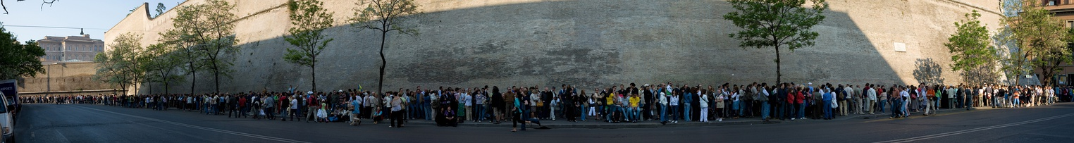 On the last Sunday of each month, the Vatican Museum is open to the public for free. This is extremely popular and it is common to wait in line for many hours. This image is a panoramic view of one small stretch of the entire queue in April 2007, which continues for some distance in both directions beyond view. In the background is the Vatican City's wall.