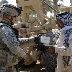 Specialist John Laursen, a Soldier assigned to 2nd Battalion, 14th Infantry Regiment, 2nd Brigade Combat Team, 10th Mountain Division, hands out boxes of medical supplies to a local Iraqi man during a joint humanitarian aid drop with the Iraqi Army.[91]