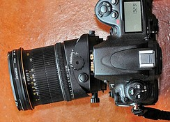 A tilt/shift lens, set to its maximum degree of tilt relative to the camera body.