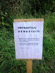 A sign in a Lithuanian forest warning of high risk of tick-borne encephalitis infection