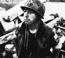 Navy Chaplain (Fr.) George Pucciarelli wears a stole over his Marine Corps camouflage uniform that he donned to deliver Last Rites after the 1983 truck bomb attack. He tore off a piece of his uniform to make a new kippa for Jewish chaplain Arnold Resnicoff, as they ministered side-by-side to all Marines