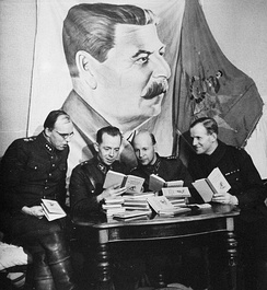 Four Finnish officers in uniform are sitting and reading Soviet skiing manuals with relaxed looks on their faces. A pile of the books is in front of them on a table and a large drape of Joseph Stalin hangs above their heads on the wall.
