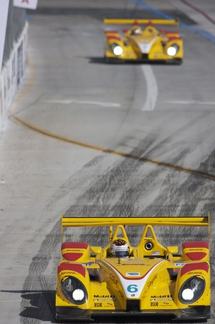 Picture of bright yellow RS Spyder racing car on a race track with another yellow car in the background
