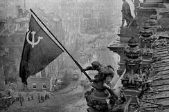 A Russian soldier raising the Soviet flag over the Reichstag during the Battle of Berlin