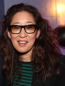 Sandra Oh smiling at the camera wearing sunglasses