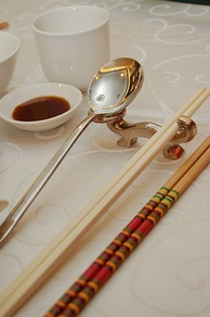 Photo showing serving chopsticks (gongkuai) on the far right, personal chopsticks (putongkuai) in the middle, and a spoon. Serving chopsticks are usually more ornate than the personal ones.