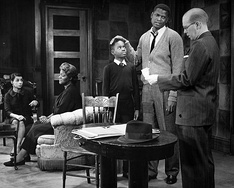 Photo of a scene from the play A Raisin in the Sun. From left: Dee, (Ruth Younger); Claudia McNeil, (Lena Younger); Glynn Turman, (Travis Younger); Sidney Poitier, (Walter Younger) and John Fiedler, (Karl Lindner).