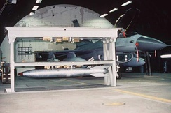 Weapons Storage and Security System vault in raised position holding a B61 nuclear bomb, adjacent to an F-16. The vault is within a Protective Aircraft Shelter.