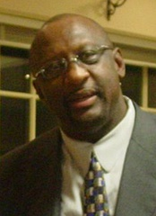 A black person, wearing a gray suit, a tie and glasses, is looking to the front.