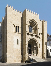 The Old Cathedral of Coimbra, Portugal, is fortress-like and battlemented. The two central openings are deeply recessed.