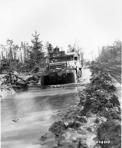 A 1st Infantry Division half-track plows its way through a muddy road in the Hurtgen Forest. 16th Infantry Regiment, 1st Infantry Division. 15 Feb 1945.