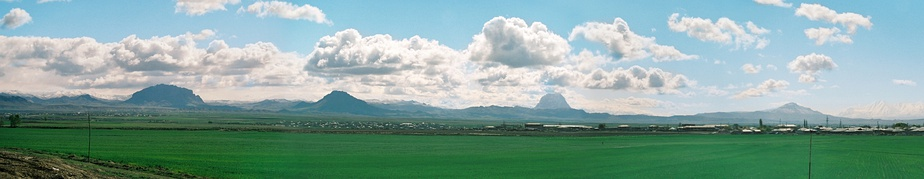 a vast green plain with isolated mountains in the distance