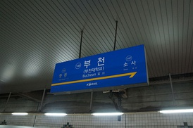 The sign with the name of the railway station in Bucheon — at the top, a writing in hangul, the transliteration in Latin script below using the Revised Romanization, along with the hanja text.