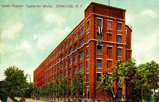 Smith Premier Typewriter Co. at Syracuse, New York c.1910 – The Smith Premier factory seen here was begun in early March 1903 and was completed in about four months. The factory was shut down around 1921 when the Smith Premier Typewriter Company was absorbed fully by Remington Typewriter Company. This is the street side view; powerhouse and rail spur are behind, on the right out of view.