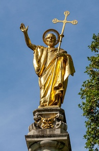 Gilt statue of Saint Paul at the top of St Paul's Cross in the cathedral precinct