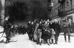 "1943 Picture of Jewish prisoners in the Warsaw Ghetto Uprising; the SS man at right has the ""Totenkopf"" insignia on his collar"