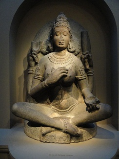 A 10th-century Yogini statue from Tamil Nadu, India. She is seated in an asana, and her eyes are closed in meditative state.