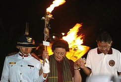 UP Diliman Corps Commander Ronald Cardema (left) and then Commission on Higher Education chair Romulo Neri (right) assist former UP President Emerlinda R. Roman as she descends from the staircase that led to the lighting of the Centennial Flame during the kickoff of the centennial celebration in Diliman.
